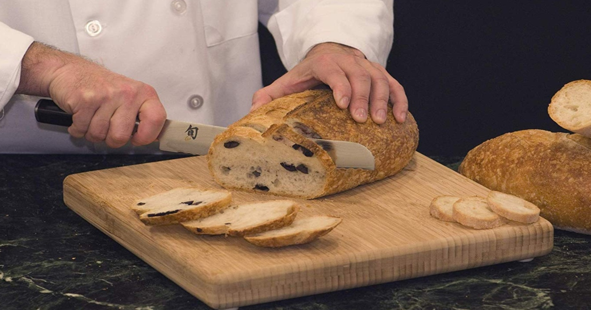 Chef holding bread and a knife, cutting the bread on a wooden cutting board, with slices of bread beside it