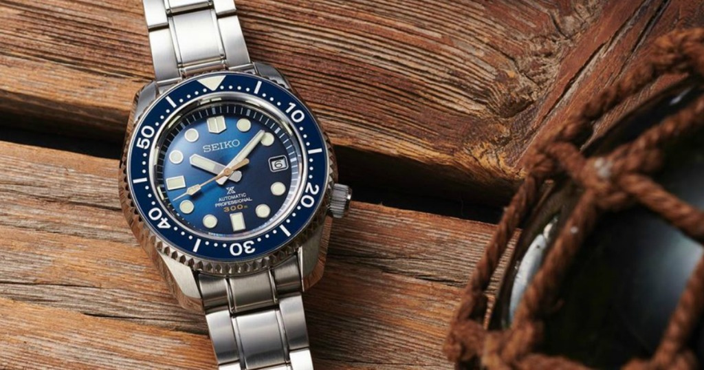 Men's silver watch with blue face on wooden background