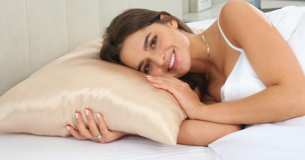 Woman laying in bed with silk pillowcase