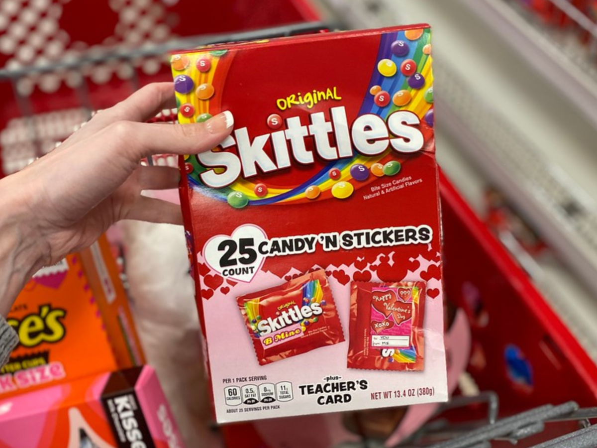 hand holding box of Valentine's Day Skittles and stickers