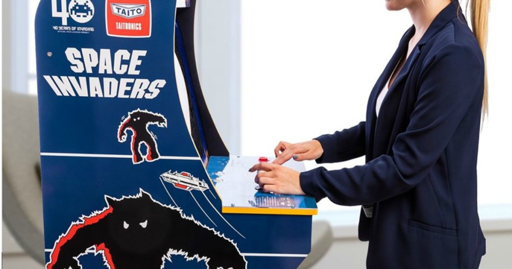 woman playing space invaders arcade game
