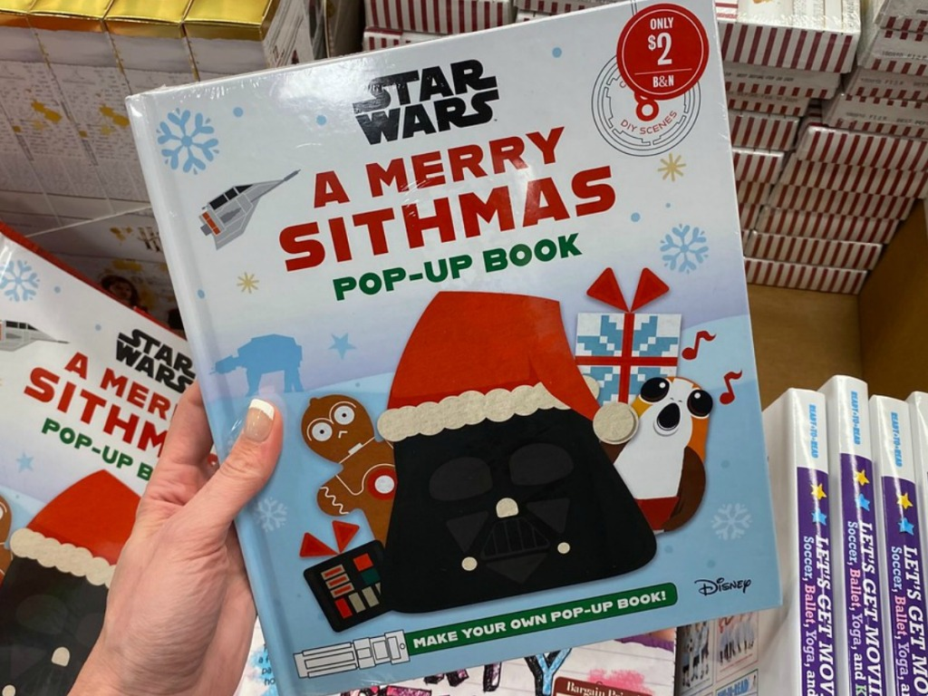 hand holding Christmas book that is Star Wars themed