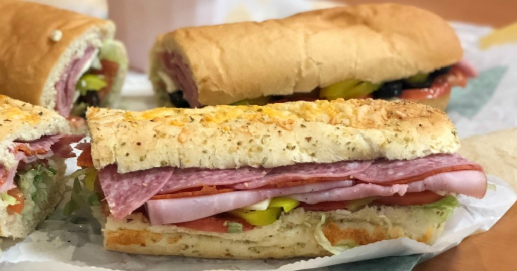 Two footlong sub sandwiches on table with drink at restaurant
