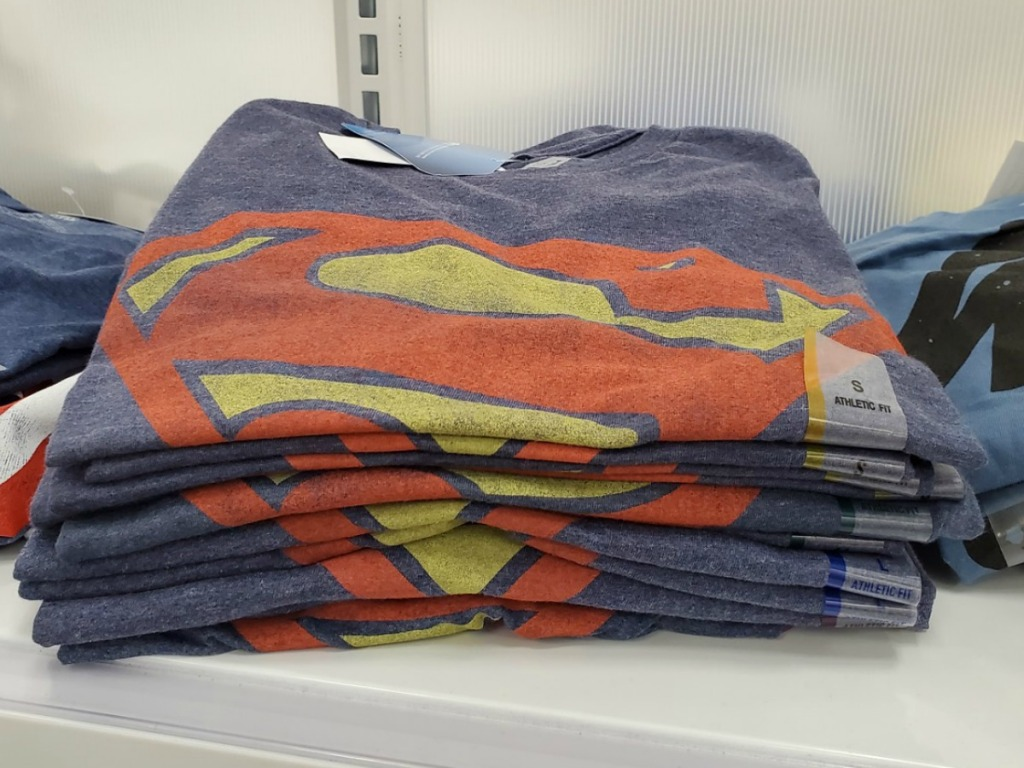 Stack of Superman themed graphic tee shirts on shelf in-store