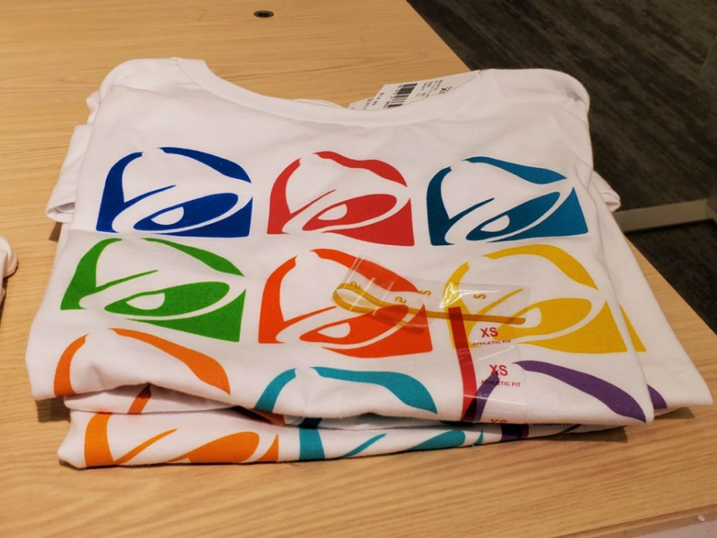 Colorful graphic tee with Taco Bell logo on wooden display table, in-store
