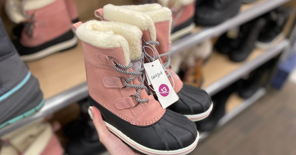 Hand holding little girl boots at Target