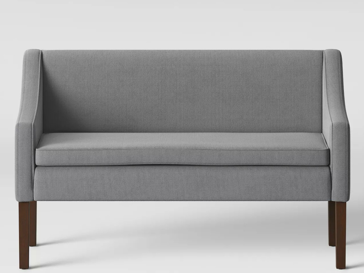 Gray settee bench with wood legs on gray background