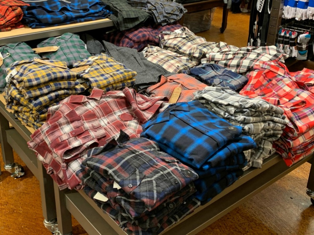 A large variety of men's flannel shirts folded and on display in-store