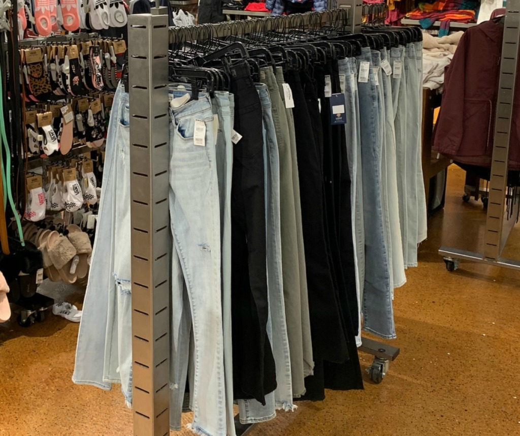 In store display of women's jeans on hangers in various shades of denim