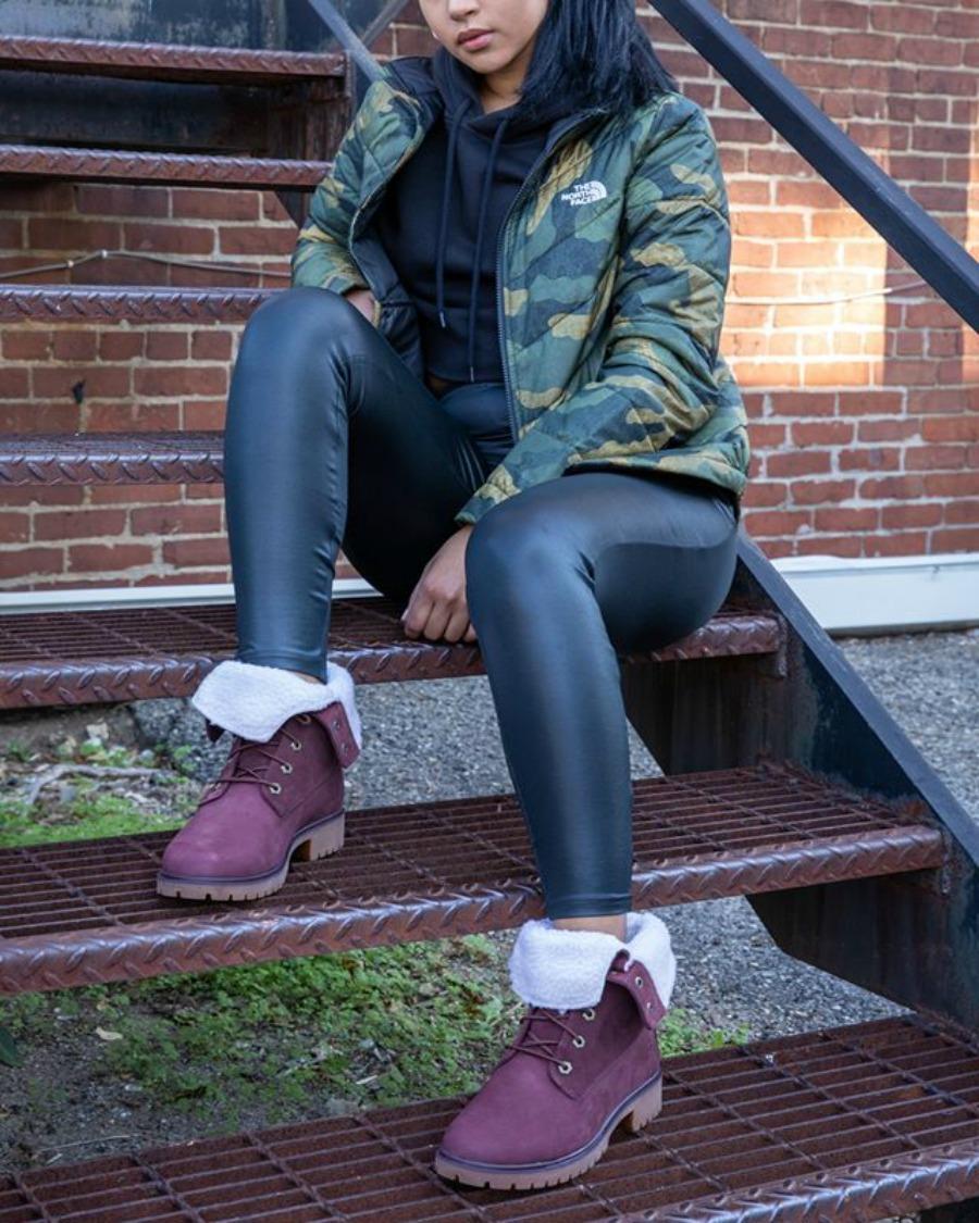 Woman wearing Timberland Jayne Fleece Boots sitting on stoop