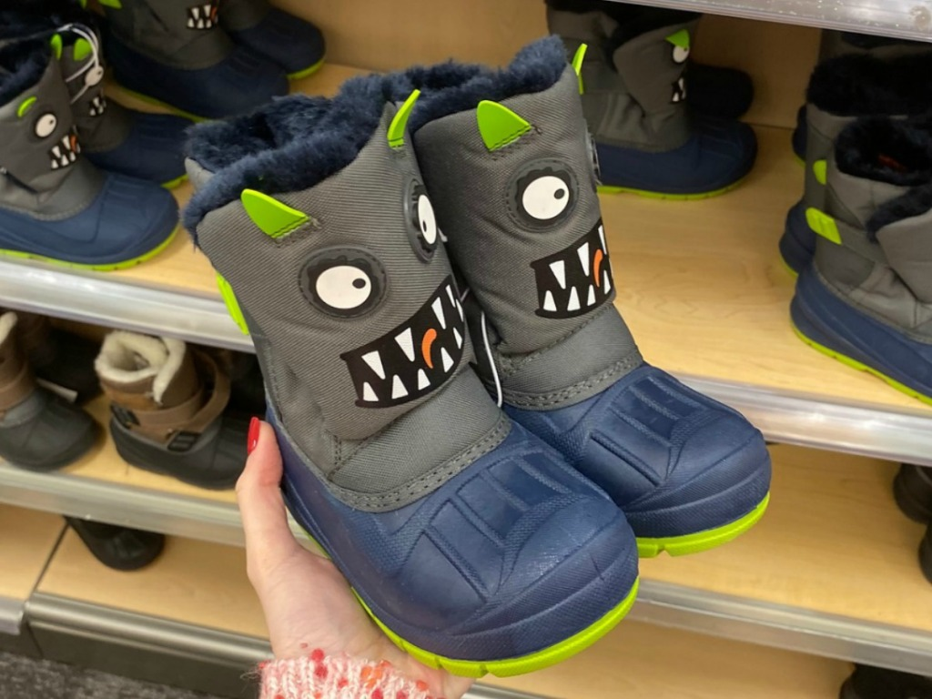 Monster themed boys boots in hand near in-store shelf