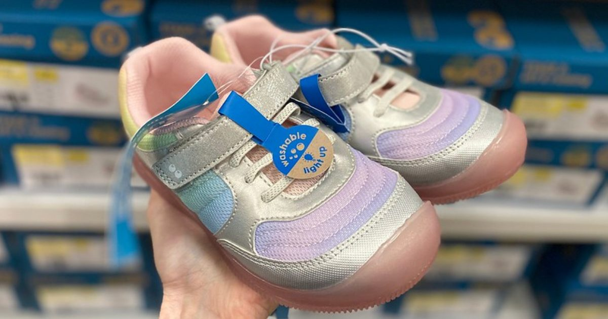 Woman's hand holding multi-colored girls toddler shoes in store aisle