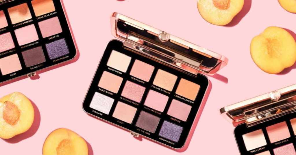 Open eye shadow palettes near fresh peaches on pink background