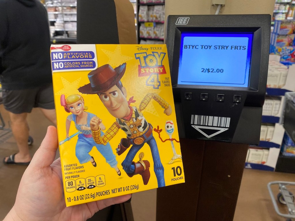 hand holding box of Toy Story fruit snacks by price scanner