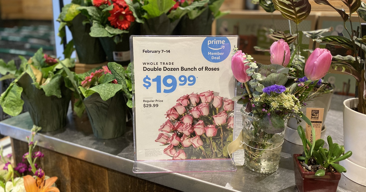 Whole Trade Roses on display in store with pricing sign in the middle
