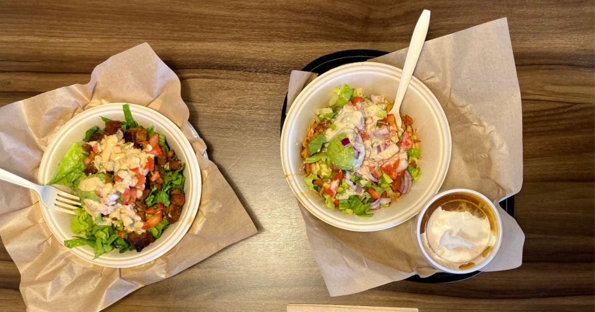 two qdoba meals on table with drink