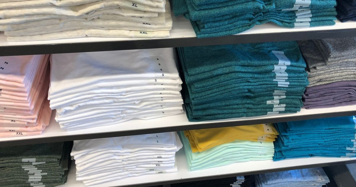 shelf with stacks of folded t-shirts in various colors