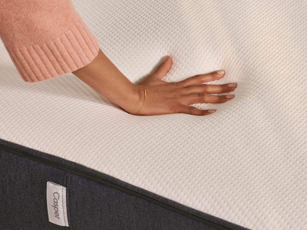 woman's hand pressing on mattress to test firmness