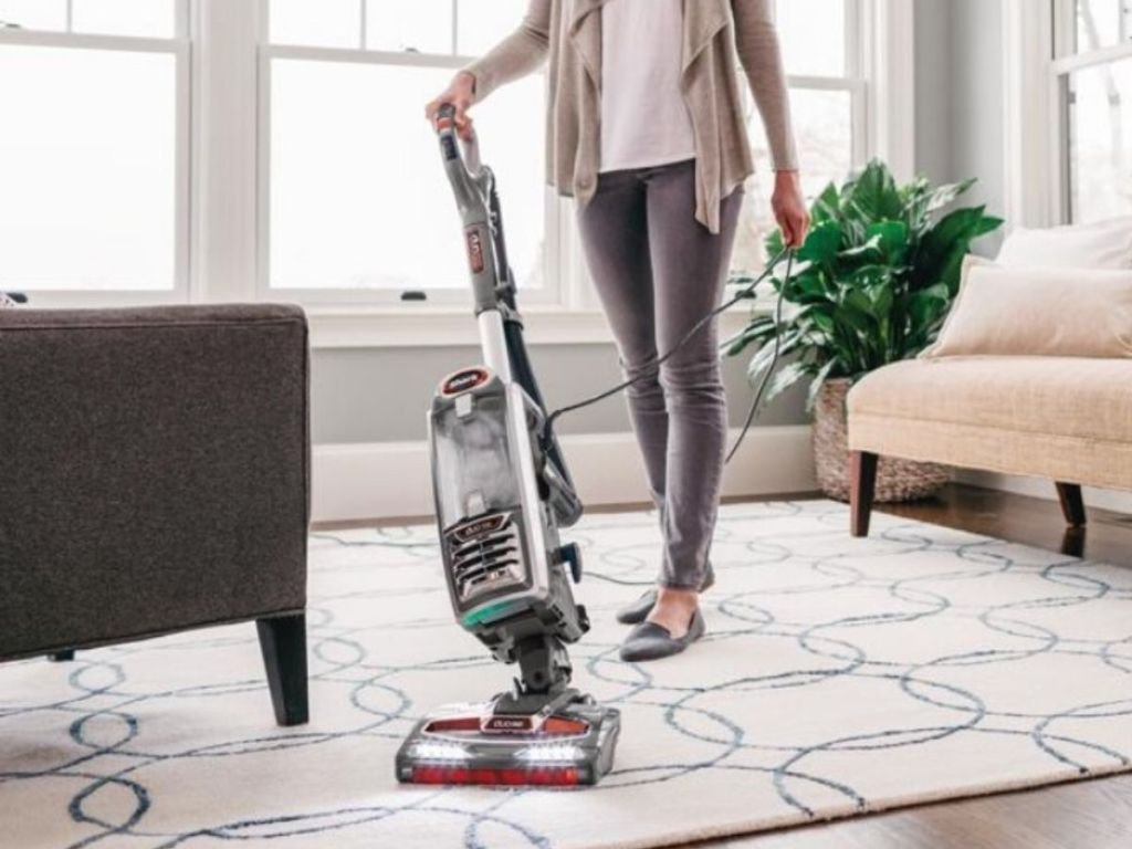 woman vacuuming carpet in living room with couches and pottedplant