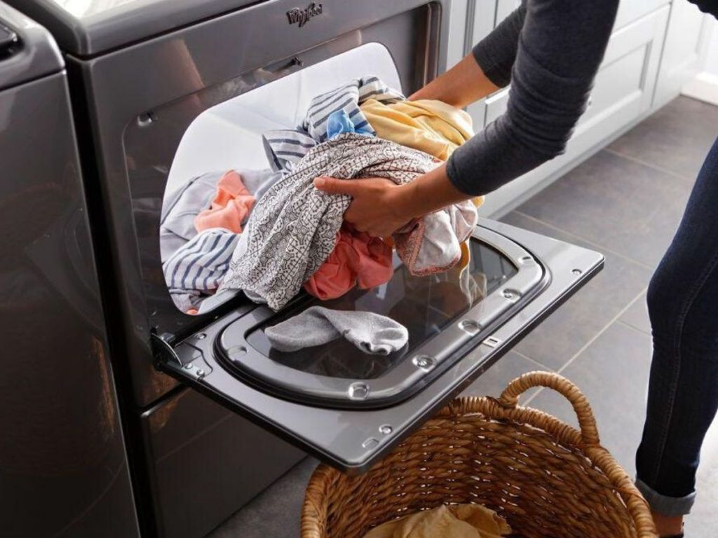 woman unloading clean clothes from dryer into a wicker basket