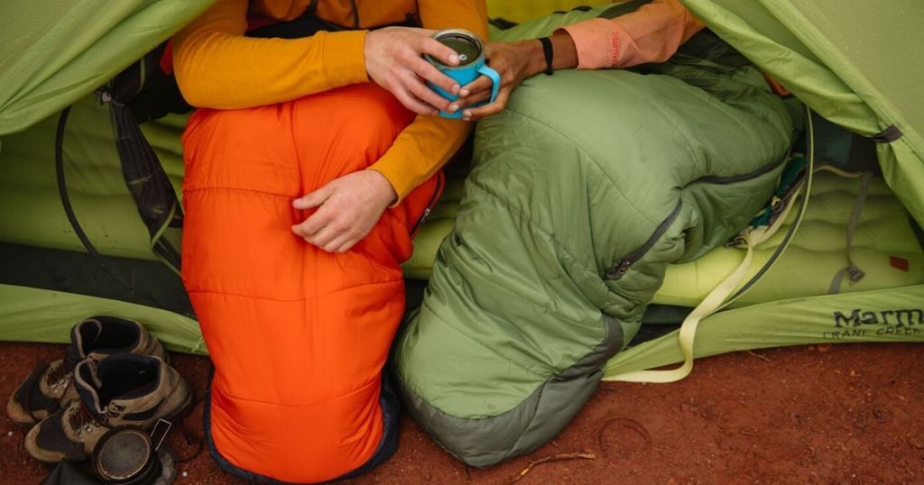 lower bodies of people sharing coffee with legs inside sleeping bags sitting in a tent