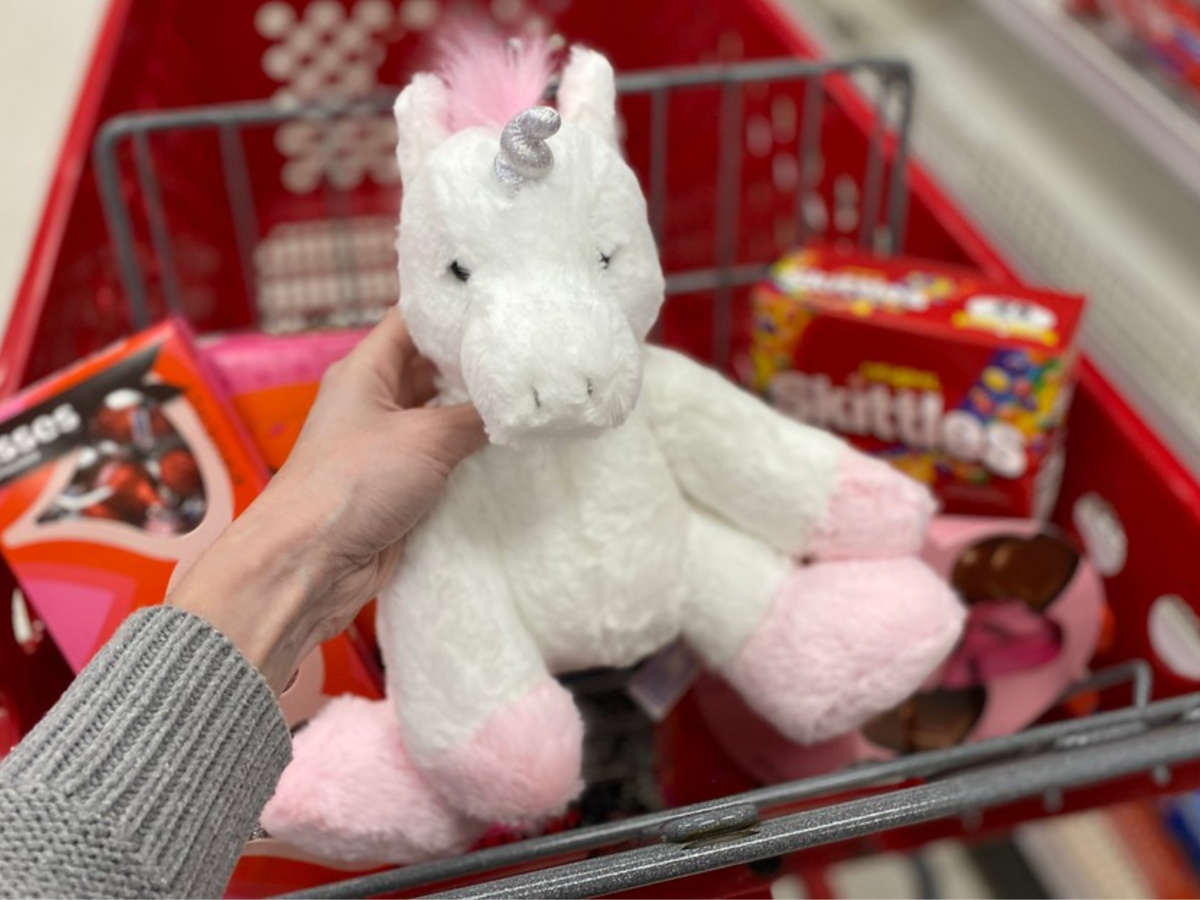 hand holding white and pink unicorn plush