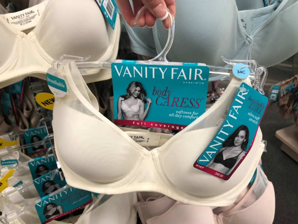 Hand holding up a white bra on a hanger near in-store intimates display