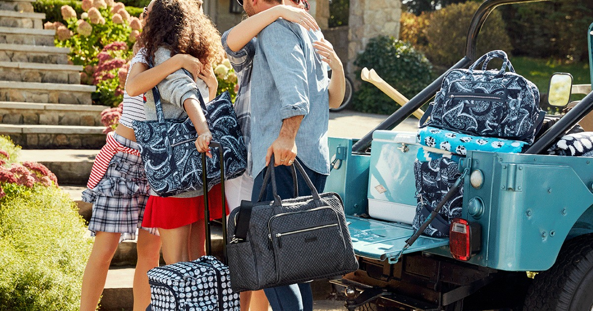 people hugging next to a jeep with suitcases and bags