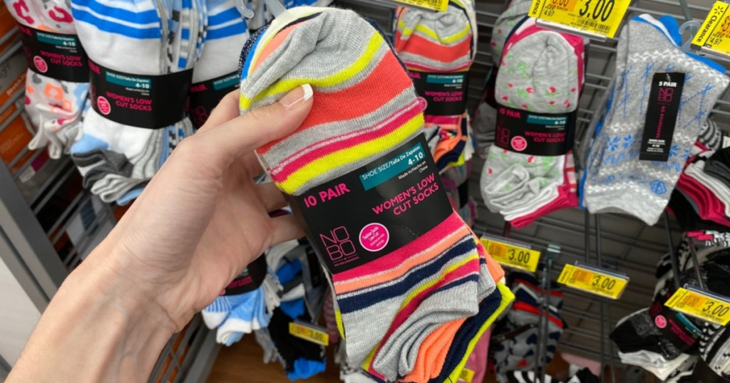 Woman holding pack of socks in store