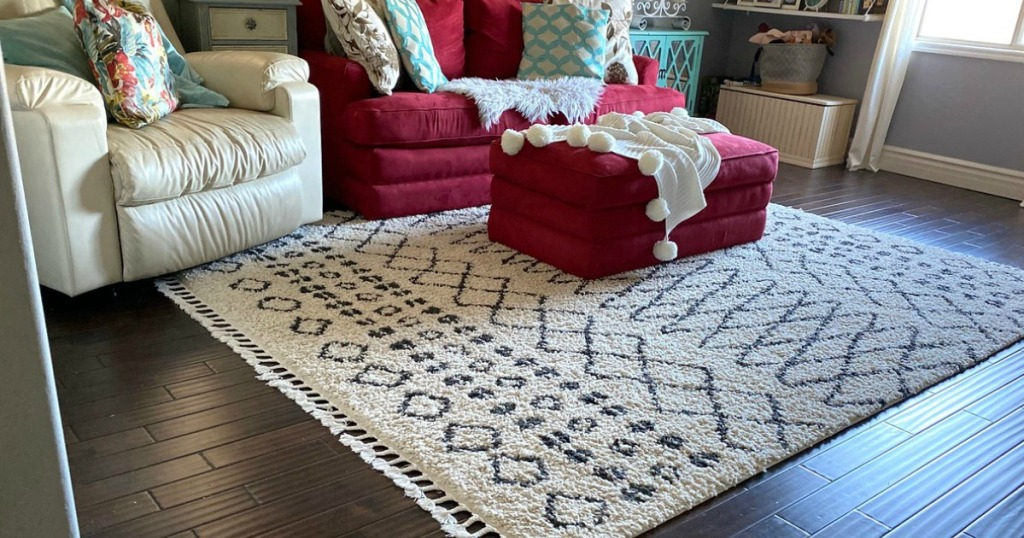 cream colored area rug sitting on a hardwood floor with red and cream furniture