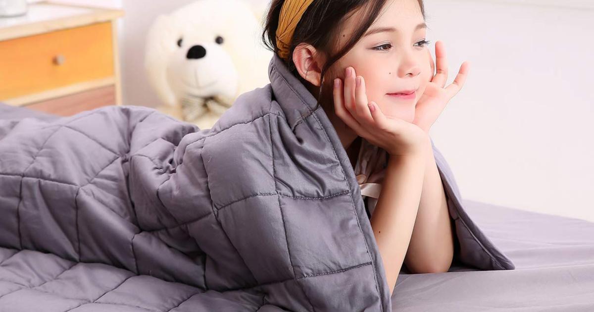 Buzio Weight Blanket on top of little girl