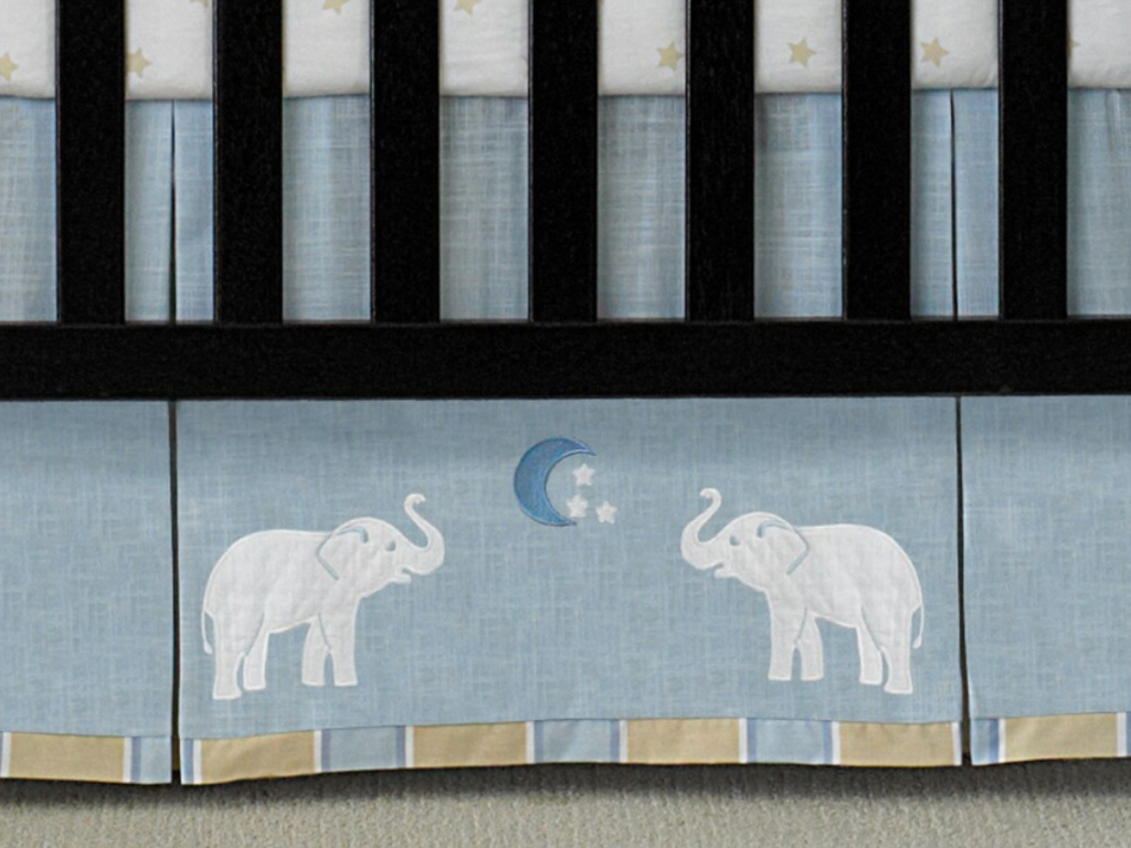 close up of crib bed skirt with elephant theme