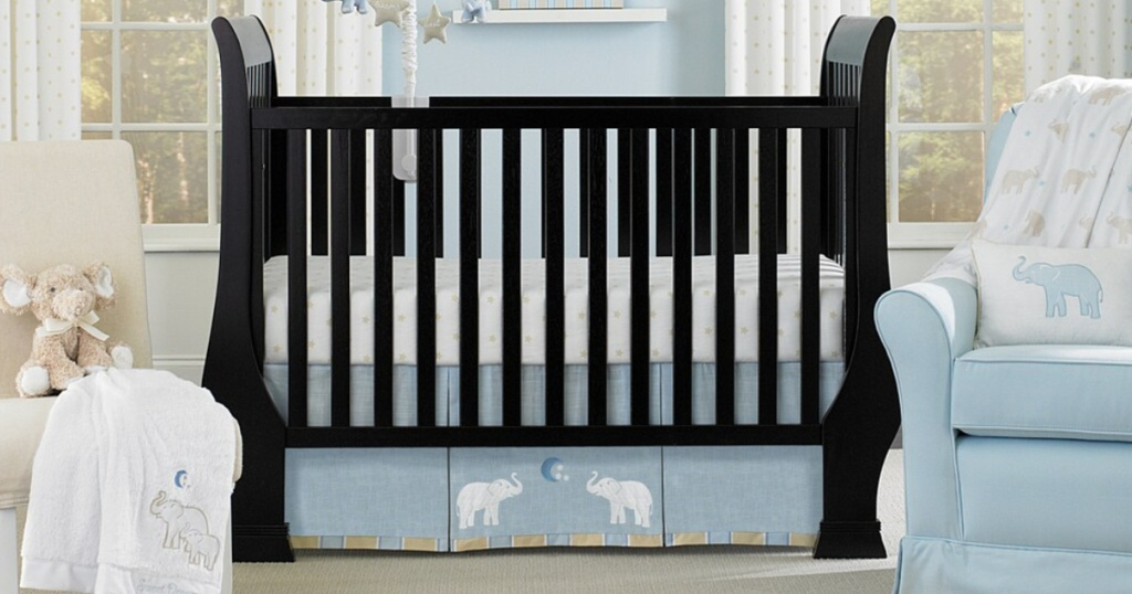 brown crib in nursery with blue and tan chairs and elephant themed blankets