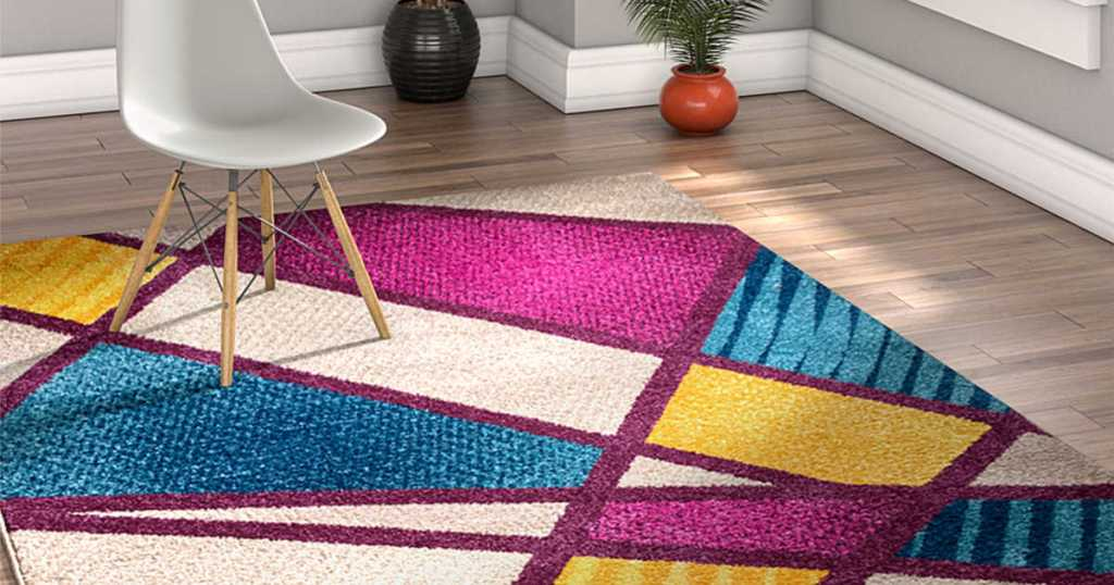 White, Pink, Purple, Blue, and Yellow geo area rug in house with white chair and plant