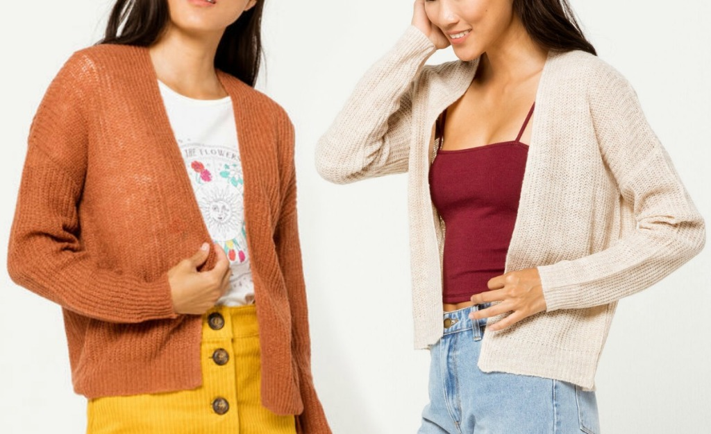 Two women wearing different colors of cardigans