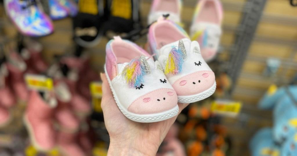 woman hand holding wonder nation baby unicorn slippers