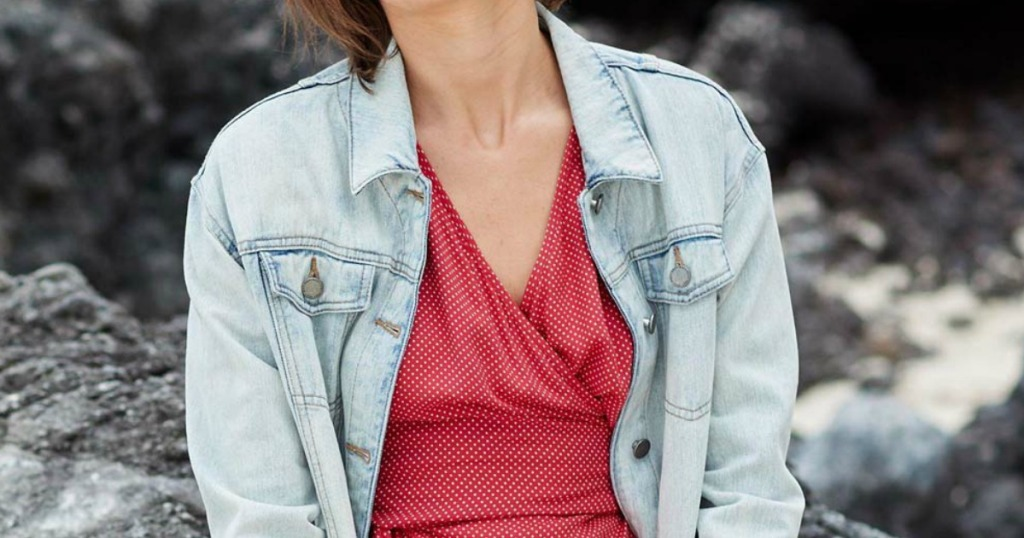 Woman sitting on a rocky terrain outdoors, wearing a bleached denim jacket and red dress