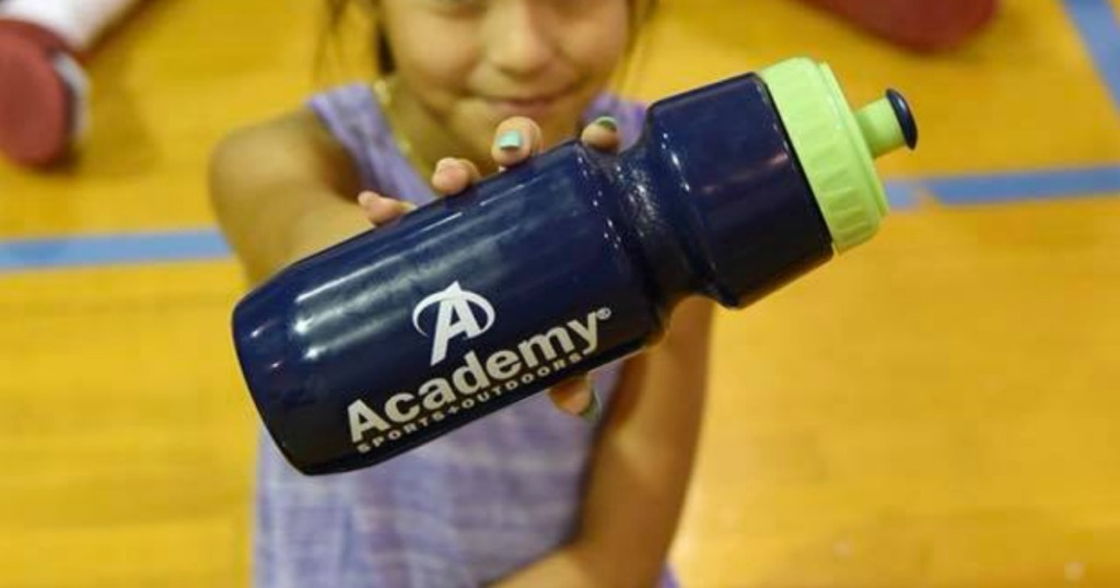 girl holding water bottle with store logo on it