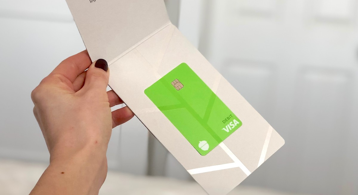 hand holding a green visa card in white pamphlet
