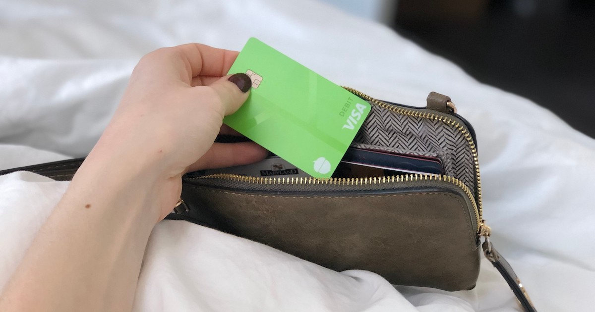hand holding a bright green visa card with wallet
