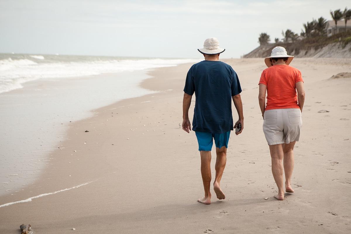 man and woman walking on sandy beach along shoreline
