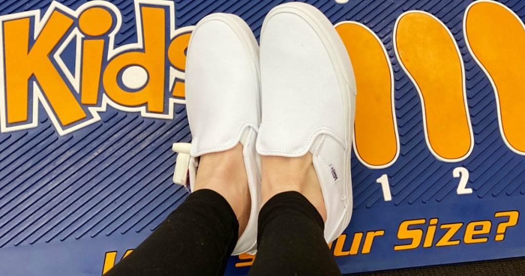 woman wearing white Vans kids shoes
