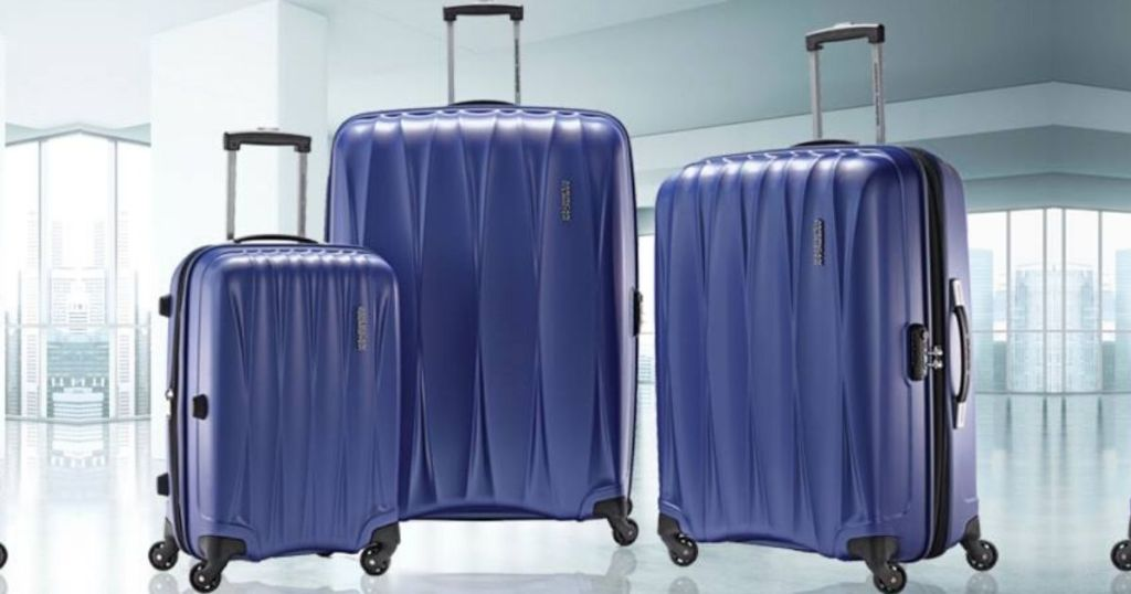 3 pieces of assorted size hard shell luggage on wheels with handles in airport