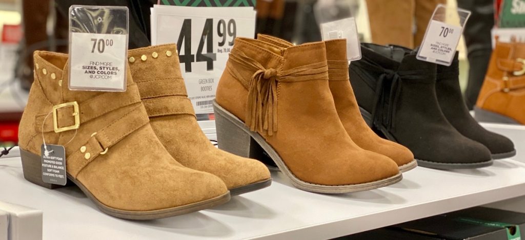 three pairs of boots on shelf at store