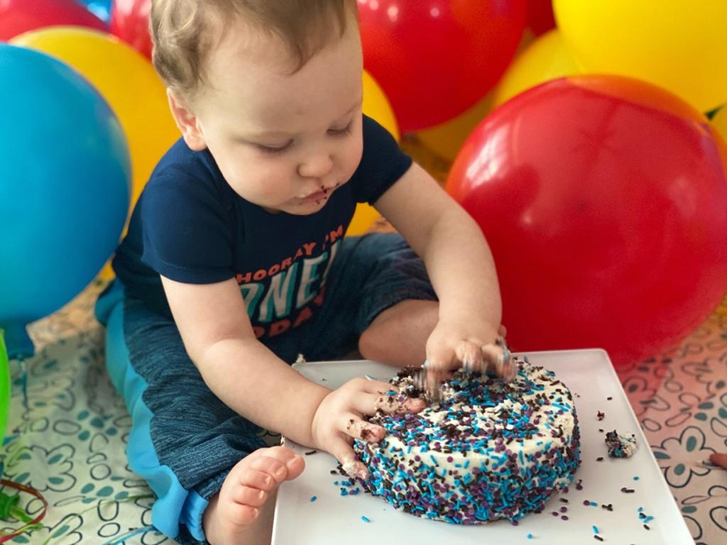 baby boy putting hands into smash cake