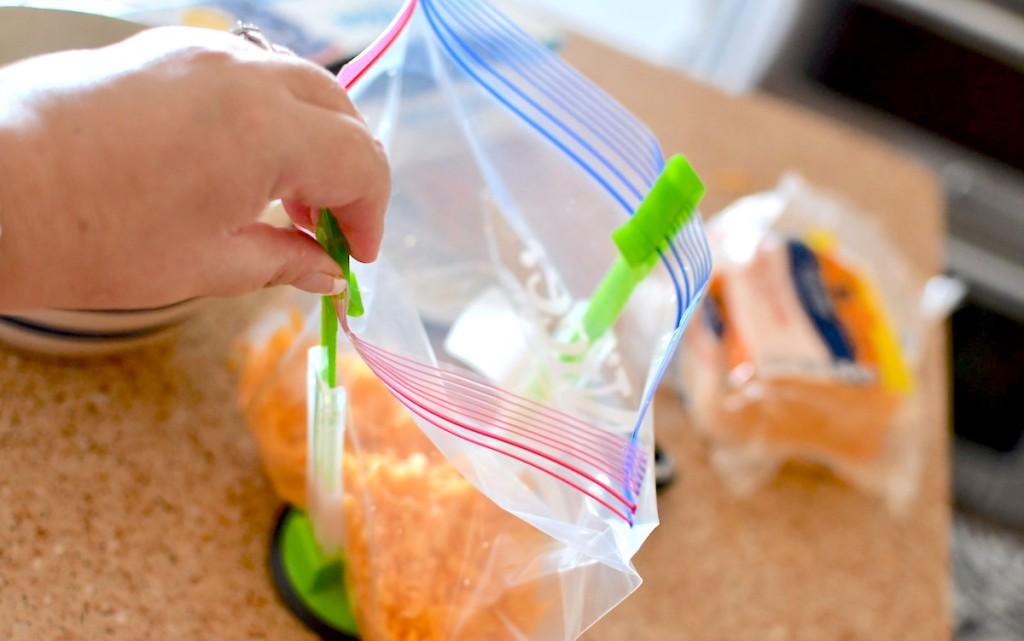 hand holding a ziploc bag open with green and clear stand