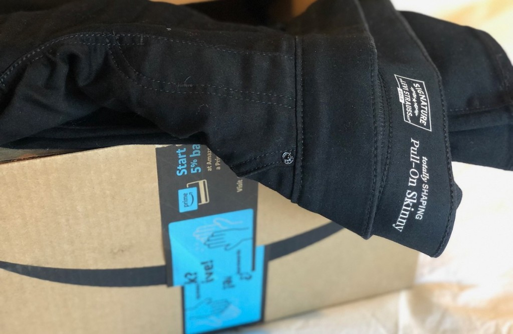 black pair of jeans sitting in Amazon box
