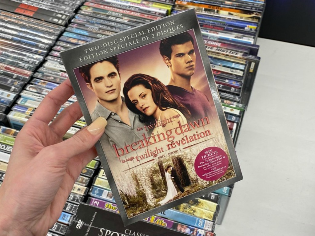 hand holding DVD movie by store display