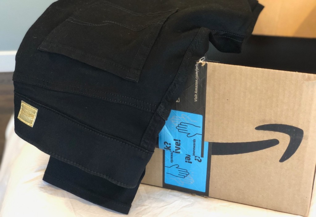pair of black jeans sitting in amazon box