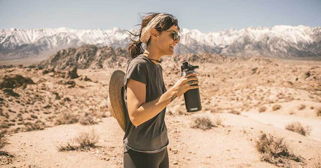 woman holding a stainless steel water bottle in the desert